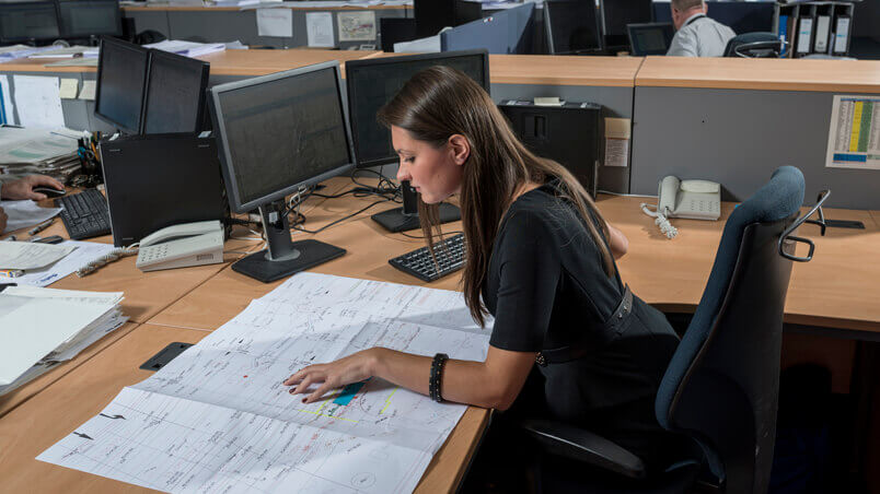 Female engineer reviewing technical drawings