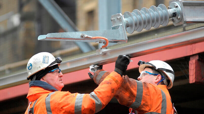Rail workers installing new electrification equipment