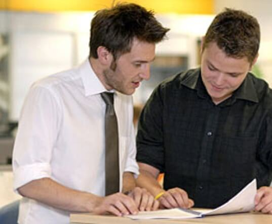 Two men discussing a document