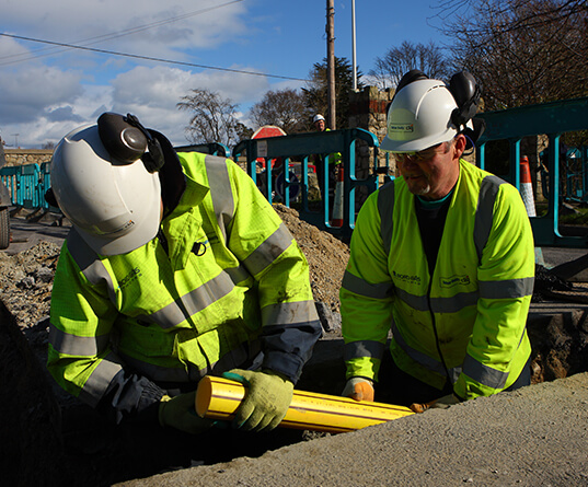 Two people installing a gas pipe